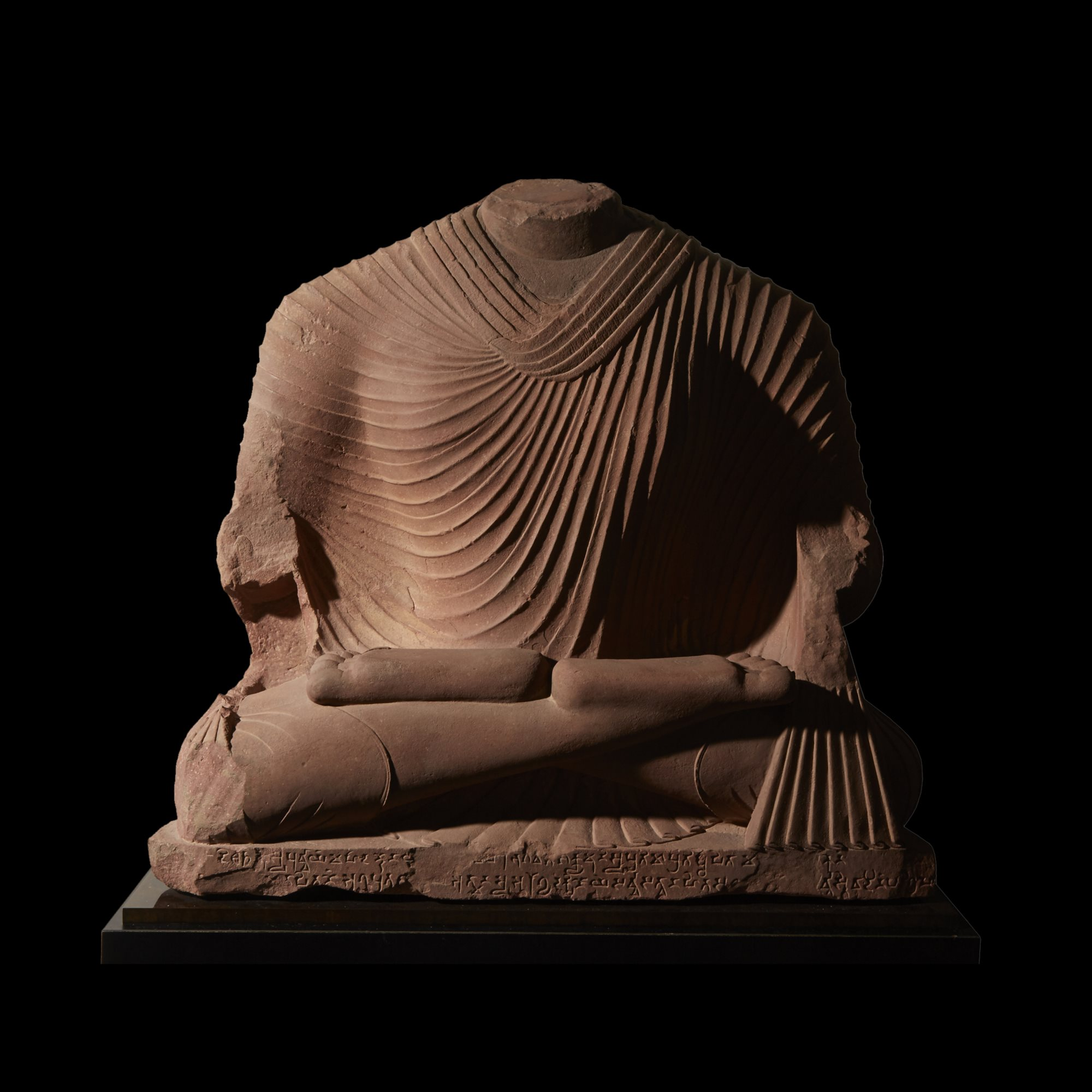 Over life-sized sculpture of Buddha, Mathura, Kushana period 1st - 2nd  century AD, Pink sandstone,  H: 37, W: 40 in. (mounted), Estimate: $30,000-50,000. Offered in The Jeff Hunter Collection | Antiquities & Tribal Art on March 13, 2019.