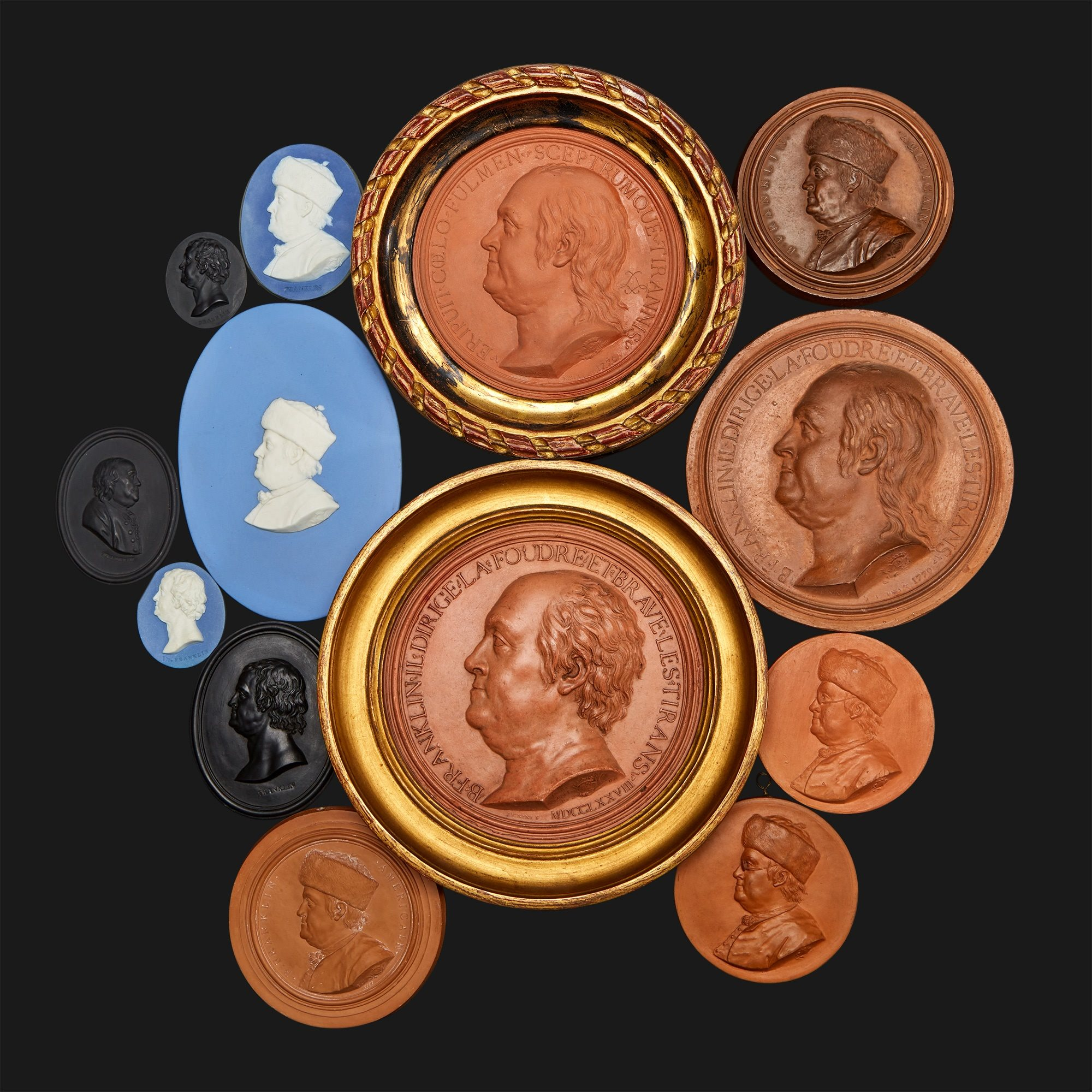 a collection of clay portrait medallions depicting Benjamin Franklin