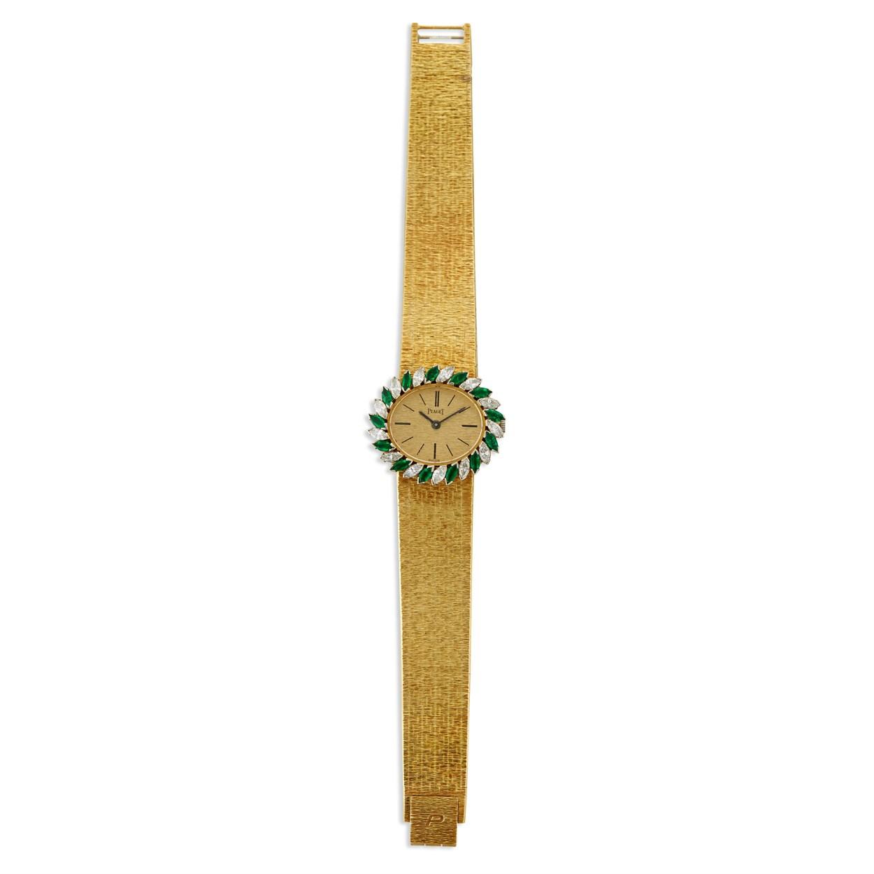 Lot 149 - An eighteen karat gold, diamond, and emerald bracelet wristwatch, Piaget