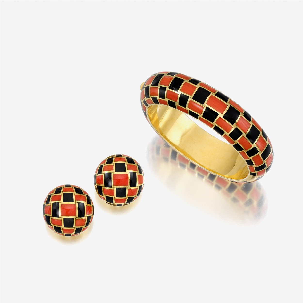 Lot 99 - An eighteen karat gold, coral, and black jade bangle with matching earrings,  Tiffany & Co.