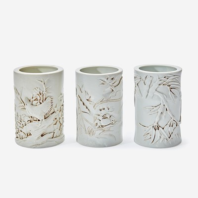 Lot 41 - Three Chinese molded and carved porcelain brushpots 瓷塑雕刻笔筒一组三件