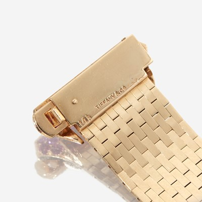 Lot 66 - A fourteen karat gold, ruby, and diamond strap bracelet, Tiffany & Co.