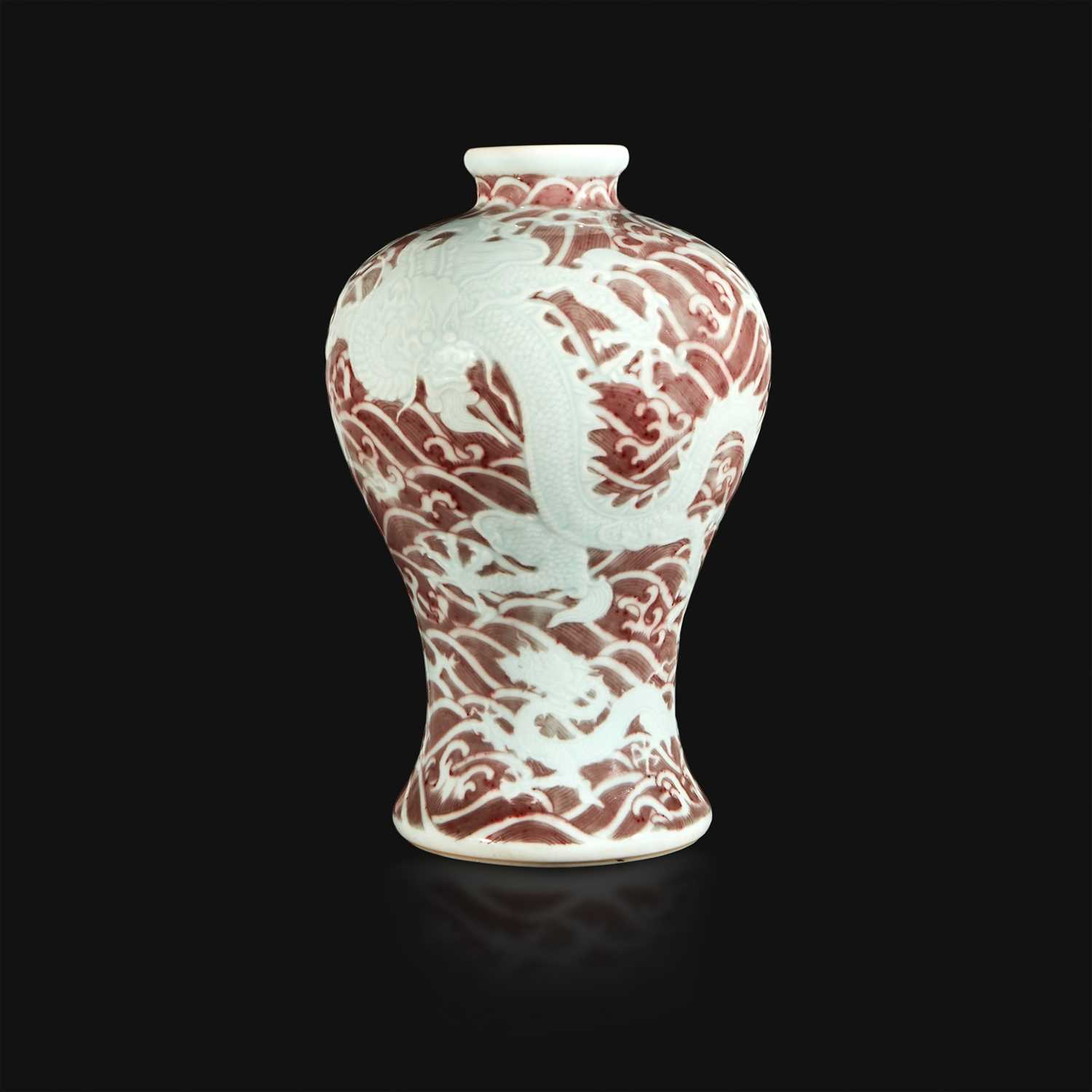 "Lot 12 - A Chinese carved and underglaze red ""Dragons and Waves"" vase, Meiping"