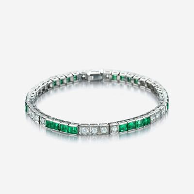 Lot 13 - An eighteen karat white gold, diamond, and green stone line bracelet
