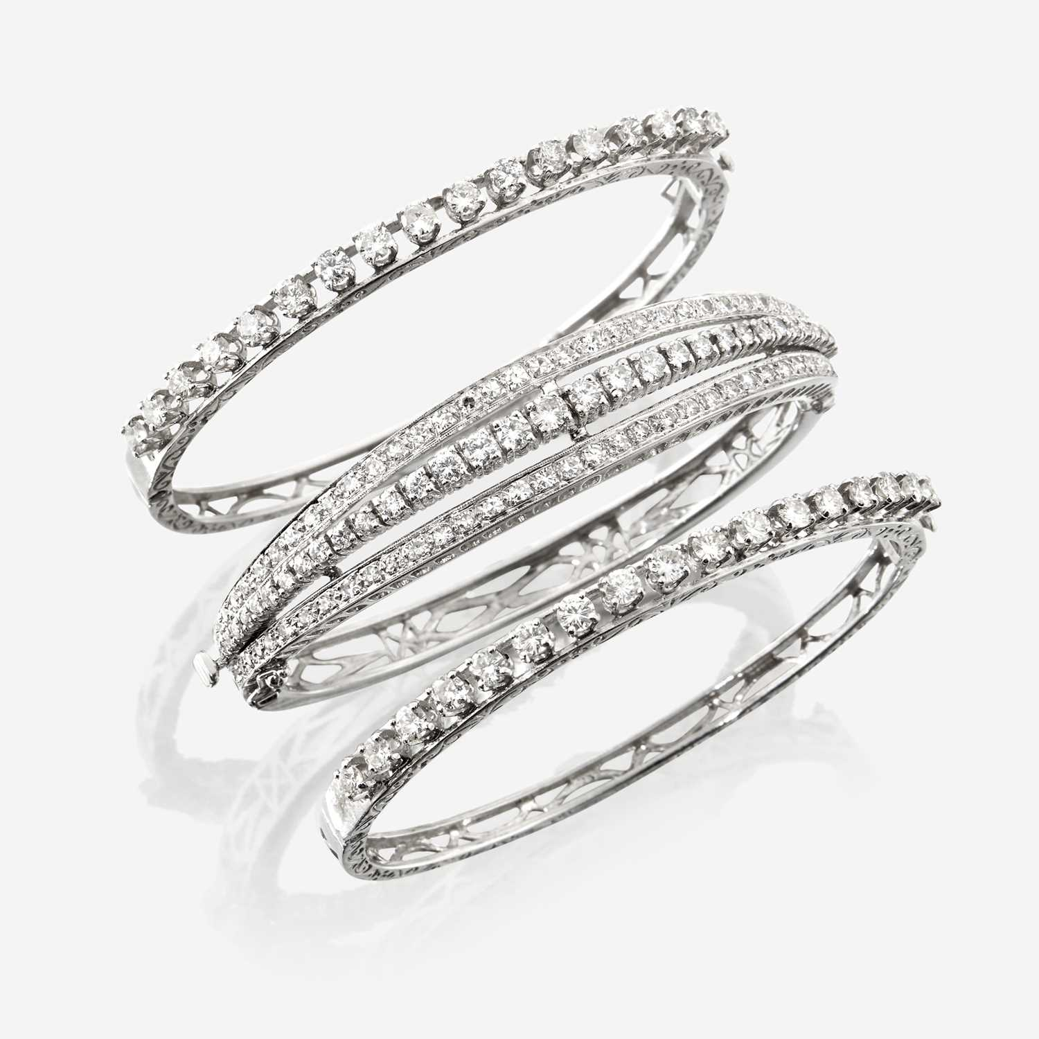 Lot 54 - A collection of three diamond and fourteen karat white gold bangles