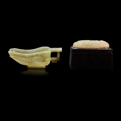 """Lot 103 - A Chinese celadon jade libation cup, Yi, and a carved grey-white jade oval """"Dragon"""" plaque"""