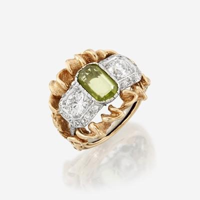 Lot 7 - A peridot, diamond, and eighteen karat white gold ring with fourteen karat yellow gold sleeve