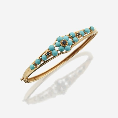 Lot 145 - A fourteen karat gold, turquoise, and sapphire bangle