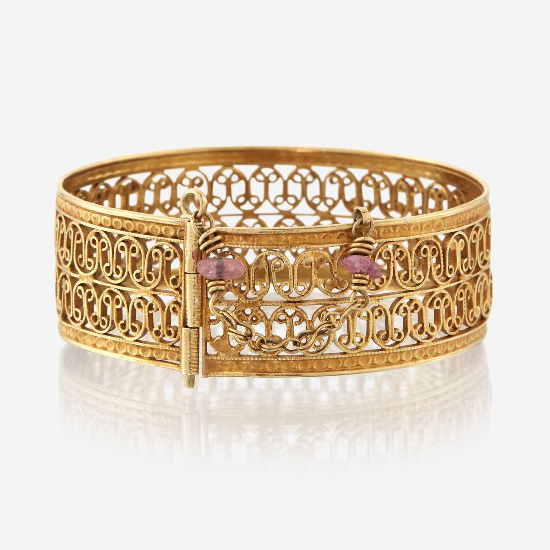 Lot 22 - An eighteen karat gold and pink tourmaline bangle