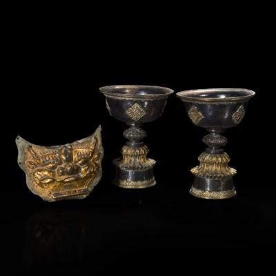 Lot 177 - A pair of Tibetan or Mongolian parcel gilt butter lamps and a gilt repoussé mask 鎏金兽面铜牌饰和鎏金灯盏一对