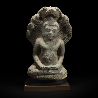 Lot 162 - A Khmer style carved stone figure of Buddha seated under a cobra canopy 高棉风格石雕眼镜蛇冠冕佛首