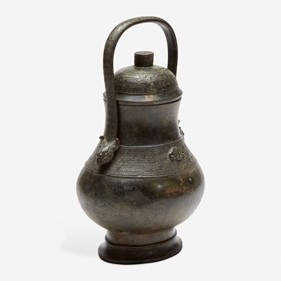 Lot 49 - A Chinese archaistic patinated bronze covered wine vessel, you 倣古风格卣
