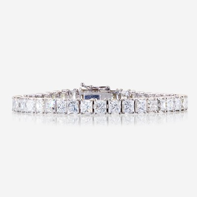 Lot 55 - A diamond and fourteen karat white gold line bracelet