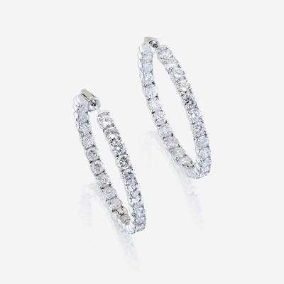 Lot 52 - A pair of diamond and fourteen karat white gold earrings